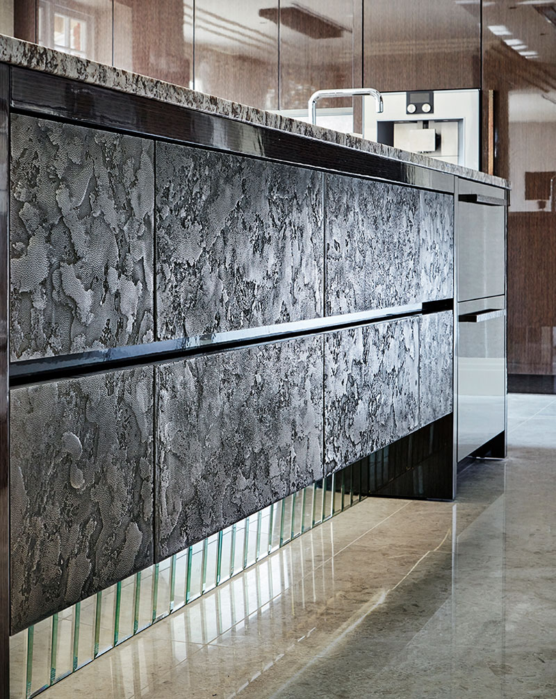 luxury kitchen island with textured drawers and LED lighting mirror plinth