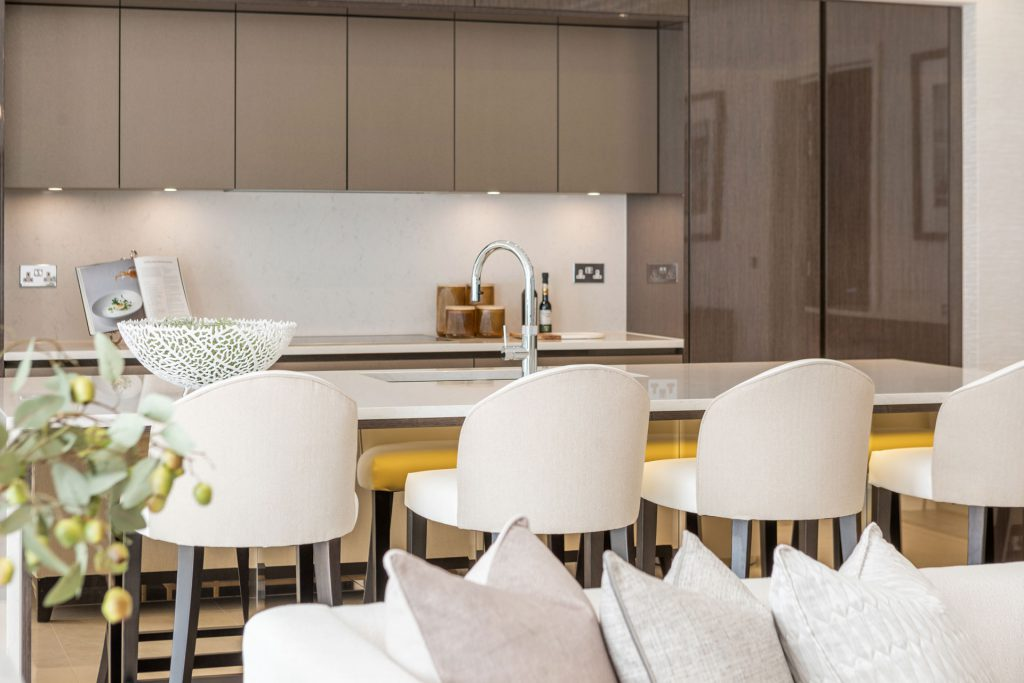 Luxury kitchen with brown cabinetry and gold mirror island